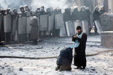 KIEV, UKRAINE - JANUARY 25: A man kneels before an Orthodox priest in an area separating police and anti-government protestors near Dynamo Stadium on January 25, 2014 in Kiev, Ukraine. Violent protests in Ukraine have spread beyond the capital as President Viktor Yanukovych held crisis talks with three key opposition leaders. (Photo by Rob Stothard/Getty Images)